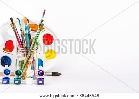 paint palette and paints brushes in glass