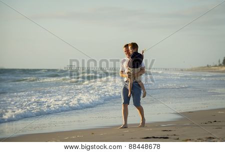 Young Happy Father Holding In His Arms Little Son Walking On Beach Sand In Front Of Sea Waves