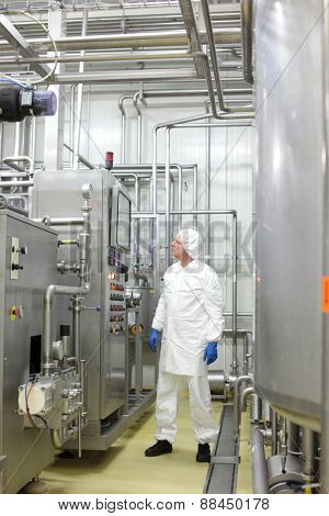 technician in white uniform is controlling industrial process in plant
