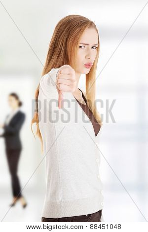Unhappy woman gesturing thumbs down.