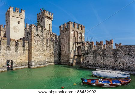 Boats on Lake Garda and medieval fortification in Sirmione, Italy.