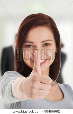 Toothy smiling woman gesturing thumbs up.