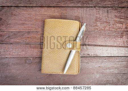 Pen On Top Of Yellow Organizer With Leather Cover On Wooden Background