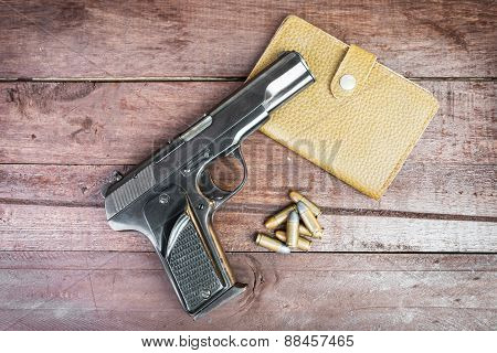 Semi-automatic 9Mm Gun And Leather Bag Isolated On Wooden Background