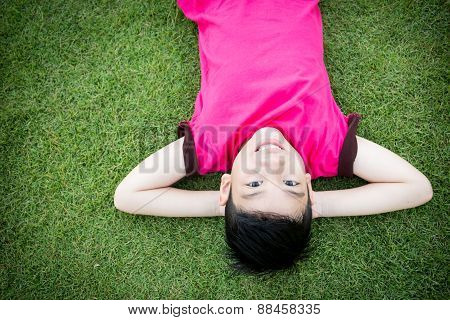 Little Asian Child Laying Down On The Grass