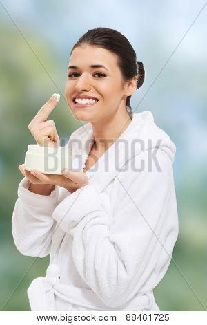 Beautiful woman in bathrobe applying face cream.