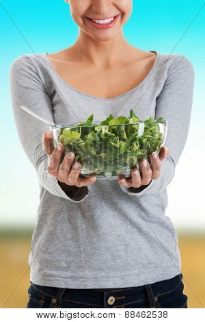 Healthy woman holding a bowl of lettuce.