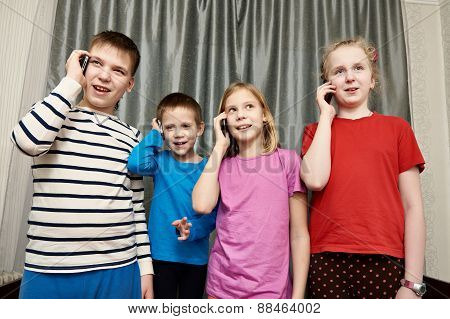 Happy Children Talking On Mobile Phones