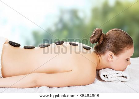 Relaxed woman recieving stone massage.