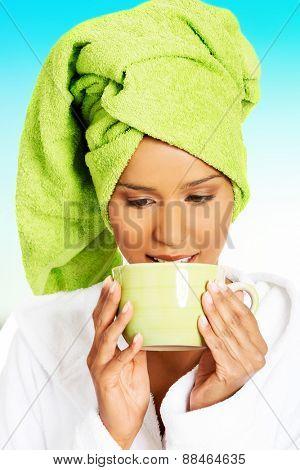Beautiful woman in bathrobe with coffee cup.