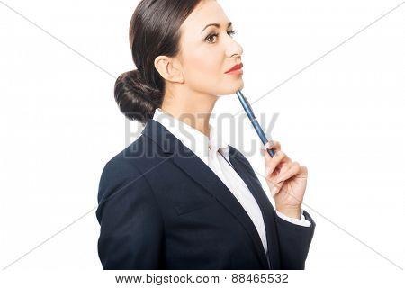 Portrait of businesswoman holding pen under chin.