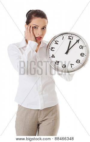 Late woman holding big clock.