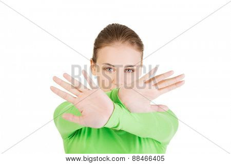 Young woman showing stop sign with both hands.