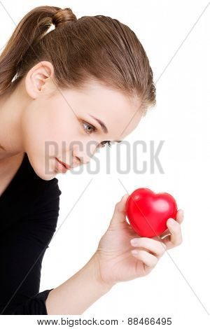 Portrait of young woman with heart model in hand.