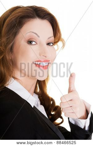 Happy smiling businesswoman with thumbs up gesture.