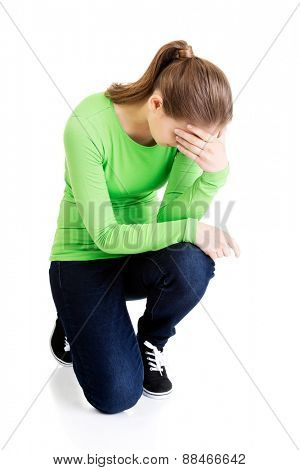 Full length young depressed woman crouching.