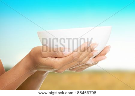 Woman hands holding empty bowl.