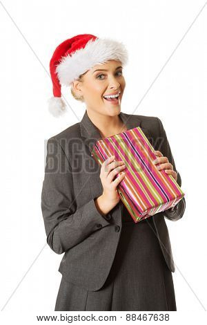 Woman weating Santa hat and holding a present.