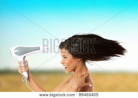 Happy smiling woman drying her hair.