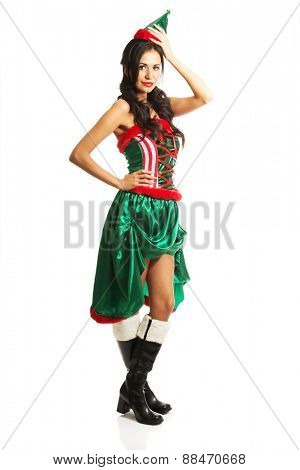 Full length woman wearing elf clothes, touching her head and hip.