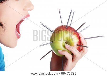 Woman eating an apple with needles, throat pain concept