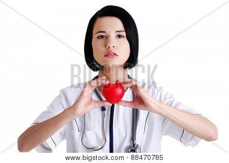 Portrait of female doctor holding heart model.