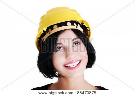 Portrait of a woman with hardhat looking up.