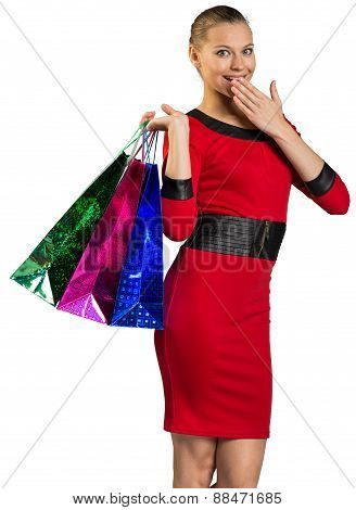 Half-turned woman covering smile, handing bags