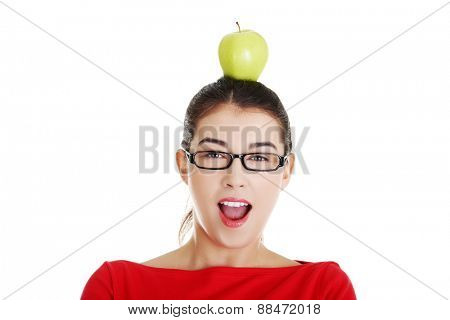 Portrait of beautiful woman with an apple on head.