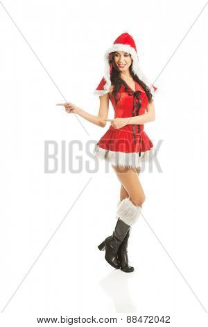 Beautiful slim woman wearing santa clothes and pointing to the right.