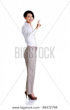 Full length businesswoman showing OK sign.