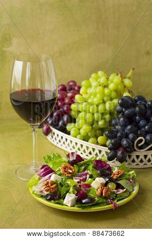 A Glass Of Wine And Salad With Grapes, Herbs, Walnuts And Blue Cheese