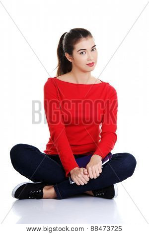Front view woman sitting cross-legged with notebook