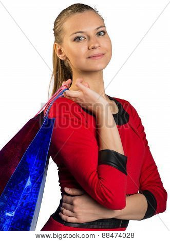 Woman with smile handing bags. Half long picture