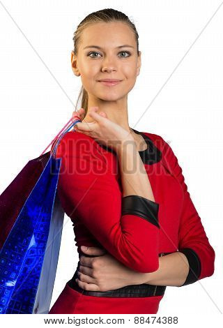 Woman with smile handing bags and hand on waist