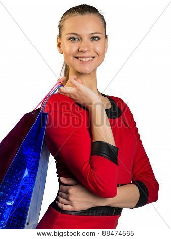 Woman with teeth smile handing bags, hand on waist