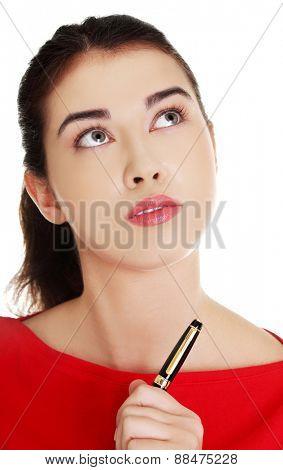 Portrait of a pensive student woman holding pen.
