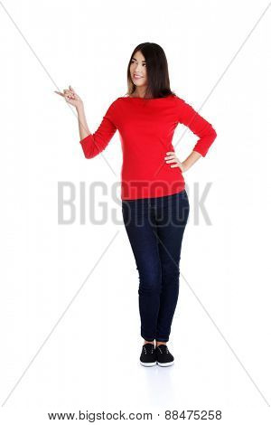 Full length woman pointing to the right.