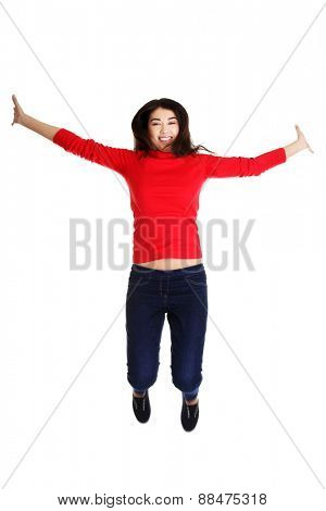 Full length cheerful woman jumping.