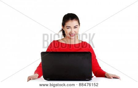 Front view woman sitting at the desk with laptop.