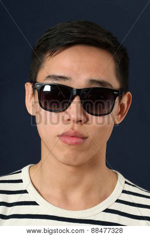 Romantic young Asian man in sunglasses