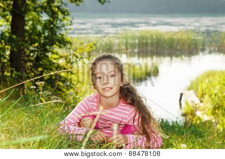 Beautiful girl dreaming near the river at sunset