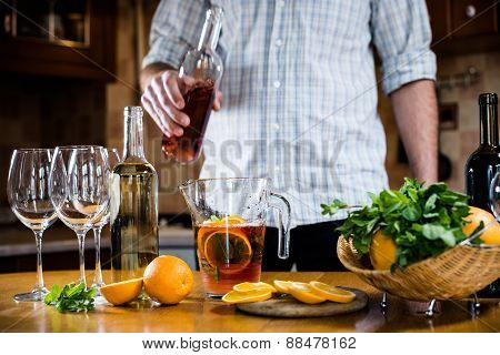 pouring red wine into a carafe