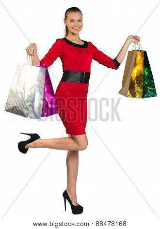 Half turned woman with right leg up handing bags