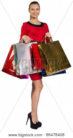 Half turned woman holding bags in two hands