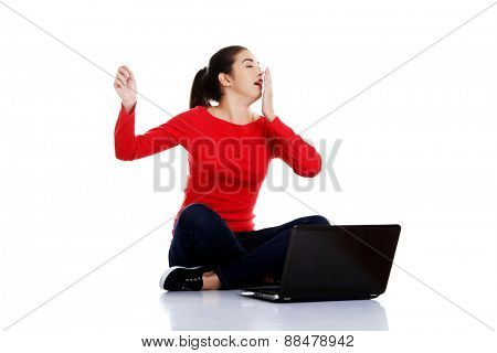 Tired woman sitting cross-legged with laptop.
