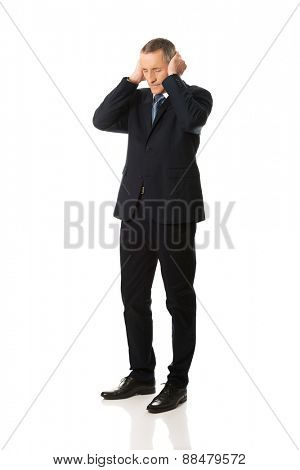 Tired mature businessman covering ears with hands.