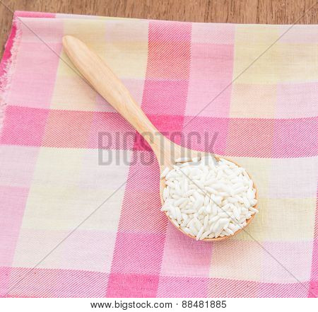 Rice In Wooden Spoon On Wooden Table