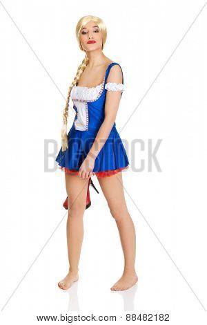 Oktoberfest woman in Bavarian dress holding her shoes.
