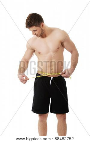 Handsome muscular man measuring his belly.